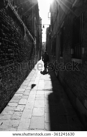 Silhouette of going on narrow street in shining sun rays. (Venice, Italy) A game of light and shadow. Light spots. Aged photo. Black and white. - stock photo