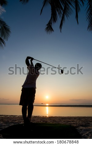silhouette of golf player action at sunset. - stock photo