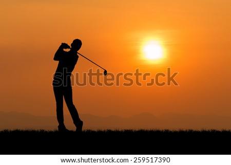 Silhouette of golfer against sunset  - stock photo