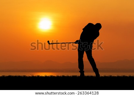 Silhouette of golfer against sunset - stock photo