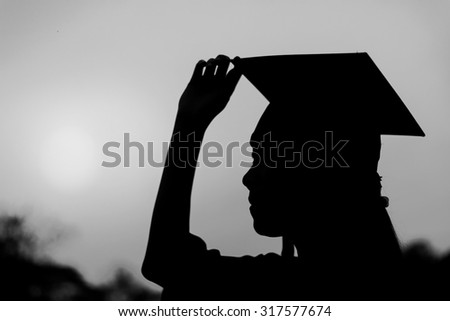 Silhouette of graduate woman in sunset , black and white - stock photo