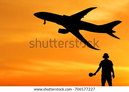 Silhouette of ground staff sending airplane taking off flight with orange sky background