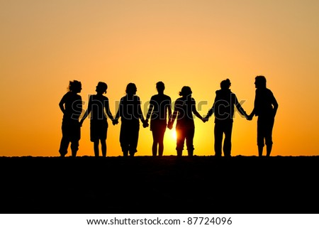silhouette of group of friends standing in sunset at beach