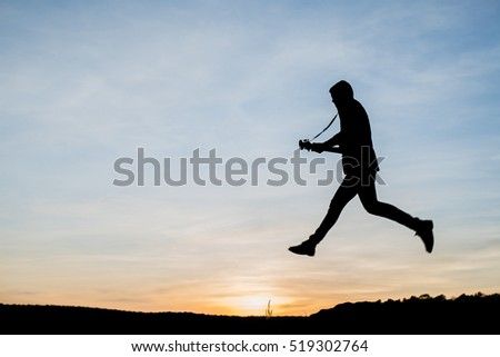 Silhouette of guitar player jump on stone. with sunset background, blue sky, lonely guitarist on the evening sundown,