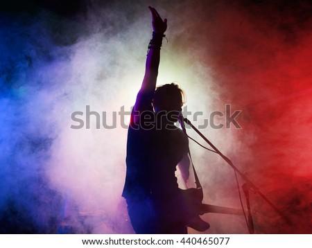 Silhouette of guitar player on stage. Dark background, smoke, spotlights