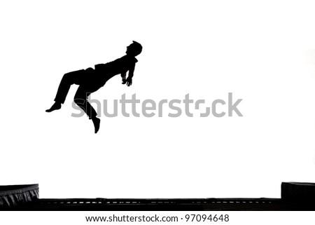 silhouette of gymnast on trampoline - stock photo