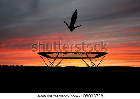 silhouette of gymnast on trampoline doing a barani - stock photo