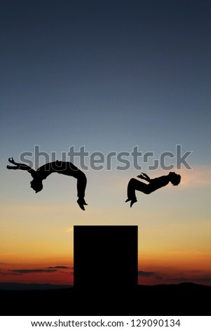 silhouette of gymnasts in sunset - stock photo