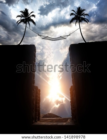 Silhouette of Hammock hanging over the abyss on palm trees at sunset cloudy sky background - stock photo