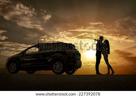 Silhouette of happiness couple stay near the new car under sky - stock photo