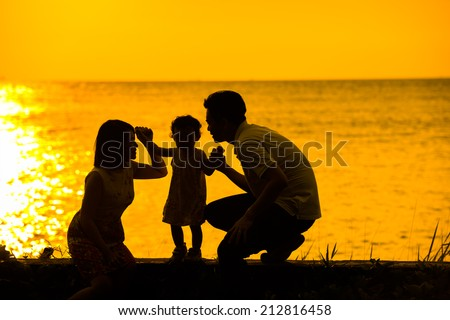 Silhouette of happy Asian family playing at outdoor beach during summer sunset. - stock photo