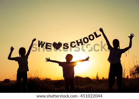 Silhouette of happy children which playing on the field at the sunset time. They having fun on the nature. Concept of the kids are ready to go to school.