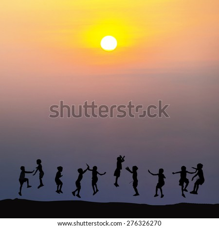 Silhouette of happy childrens jumping at sunset time - stock photo