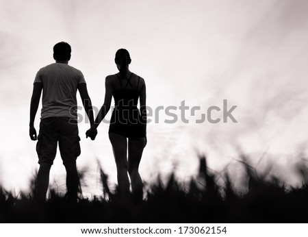 Silhouette of happy couple holding hands looking in the sunset - stock photo