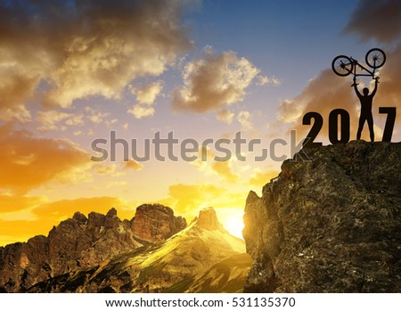 Silhouette of happy cyclist celebrating the New Year 2017 at sunset.