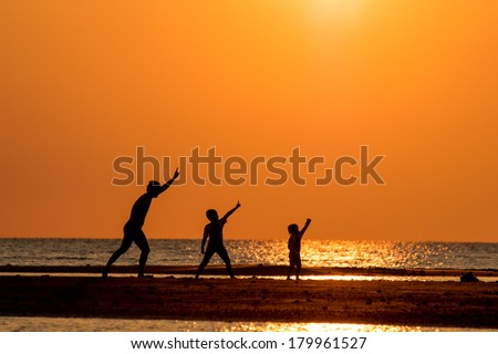 silhouette of happy family at sunset.