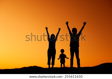 silhouette of happy family father mother and son playing outdoors at sunset - stock photo