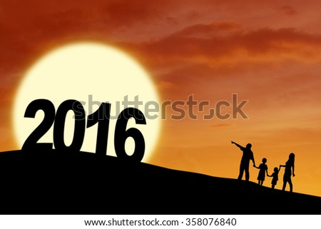 Silhouette of happy family walking on the hill while holding hands with numbers 2016, shot at sunset time - stock photo