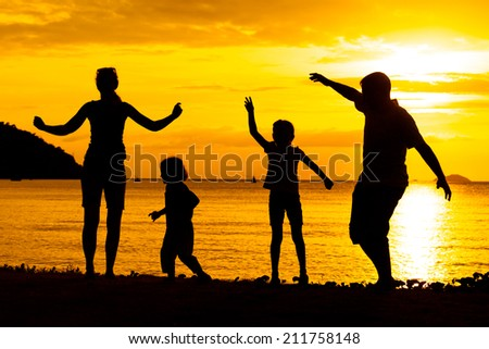 Silhouette of happy family who playing on the beach at the sunset time - stock photo