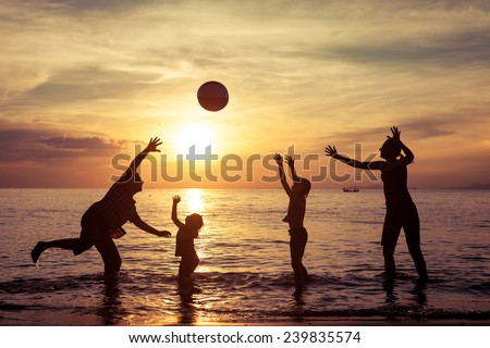Silhouette of happy family who playing with the ball on the beach at the sunset time. Concept of friendly family. - stock photo