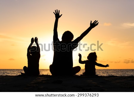 Silhouette of happy father and kids at sunset beach