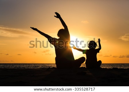 Silhouette of happy father and son at sunset beach