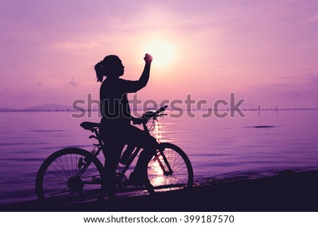 Silhouette of happy female with mountain-bike on colorful purple sky background. Active outdoors lifestyle for healthy concept. Action of winner or successful people.