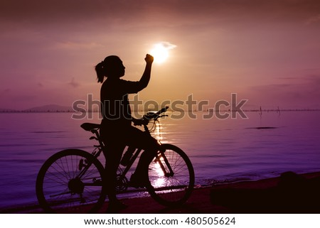Silhouette of happy female with mountain-bike on colorful sky background. Active outdoors lifestyle for healthy concept. Action of winner or successful people.