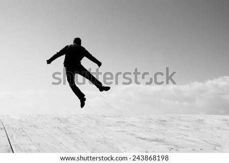 silhouette of happy jumping man - stock photo