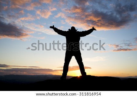 silhouette of happy man against a sunset - stock photo