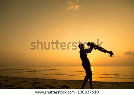 silhouette of happy man playing with daughter at the beach.