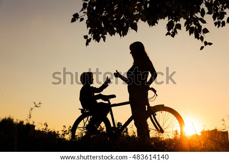 Silhouette of happy mother and son biking at sunset