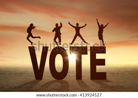 Silhouette of happy people jumping over a VOTE word at sunset time