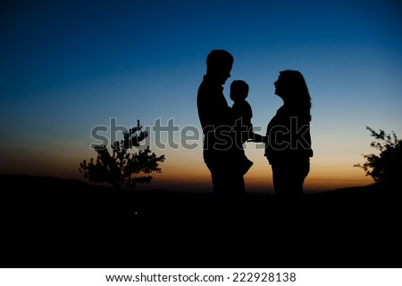 Silhouette of happy pregnant family with little boy spending time in nature