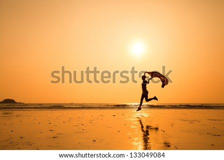 silhouette of happy running woman on the beach - stock photo