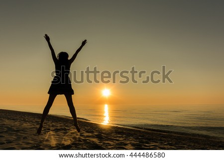 Silhouette of happy woman jumping at sunset on the beach