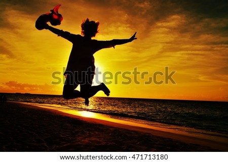 Silhouette of Happy Woman Jumping in Sea Sunset