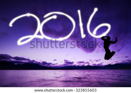 Silhouette of happy woman jumping on the beach while drawing numbers 2016