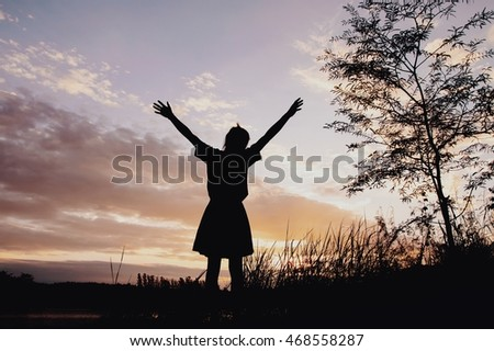 Silhouette of happy woman with sunset sky