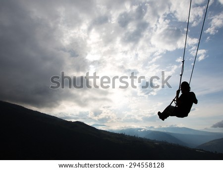 Silhouette of happy young man on a swing with a fantastic mountain view at the Casa del Arbol, Ecuador - stock photo