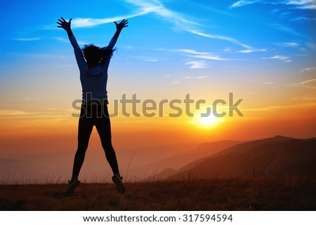 Silhouette of happy young woman jumping against sunset in the mountains
