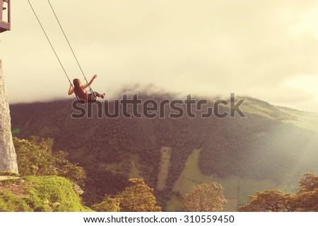 Silhouette of happy young woman on a swing, Casa del Arbol, Ecuador, vintage style - stock photo