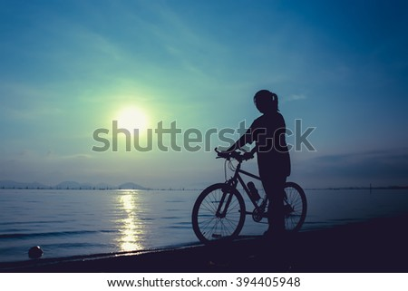 Silhouette of healthy biker-girl enjoying the view at seaside, on colorful sunset blue sky background. Reflection of sun in water. Active outdoor lifestyle concept. Outdoors.