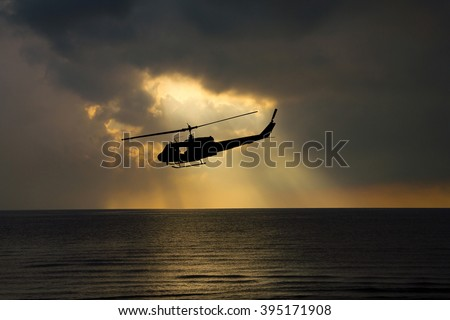 silhouette of helicopter and light sky at sunset. - stock photo