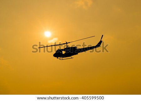silhouette of helicopter on sunset. - stock photo