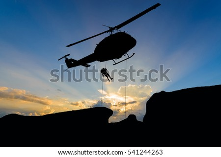 silhouette of helicopter with sunset.