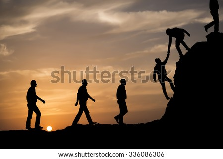 silhouette helping hand between two climberの写真素材 ロイヤリティ