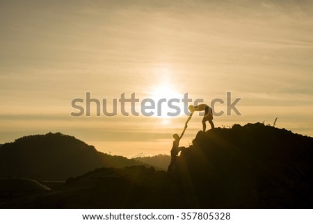 Silhouette of helping hand on mountains in sunset background. - stock photo