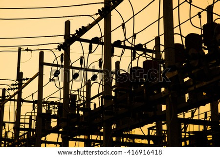 Silhouette of high power electric pole and golden sunset twilight sky