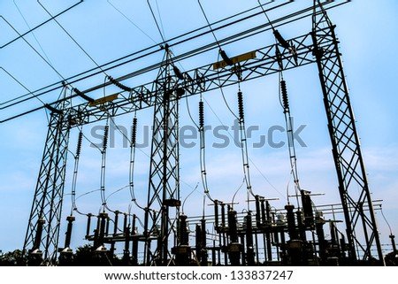 silhouette of high voltage electric pole in the power plant with blue sky
